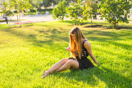 audio book: Girl listening to music streaming with headphones in summer on a meadow.