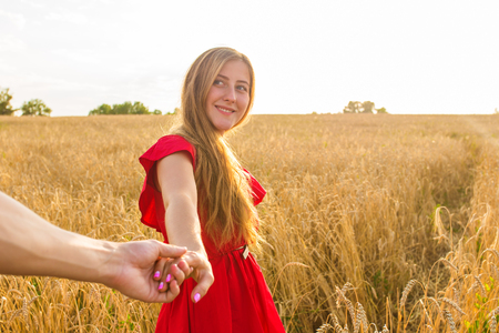 sultry: Follow me, Beautiful sexy young woman holds the hand of a man in a wheat field