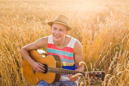 A man is playing guitar in the field at relax day with sun light. Stock Photo