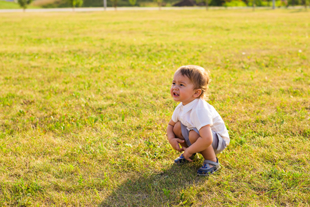 Summer, childhood and baby concept - little boy having fun in summer nature. Imagens