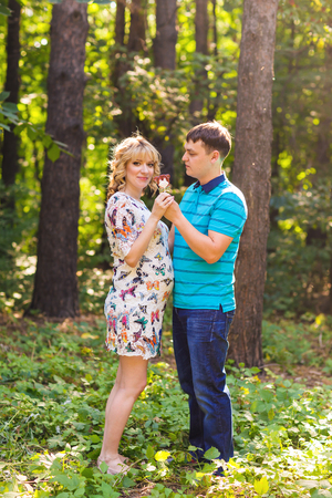 maternal: Pregnancy, family, happiness and fun concept - Man and pregnant woman have fun with candy in the park Stock Photo