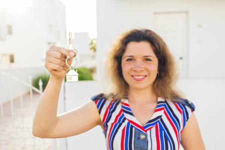 Happy house owner or renter showing keys and looking at you