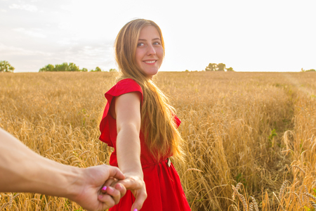 sultry: Follow me, Beautiful young woman holds the hand of man in a wheat field