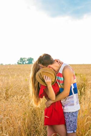 Young love couple kissing on field
