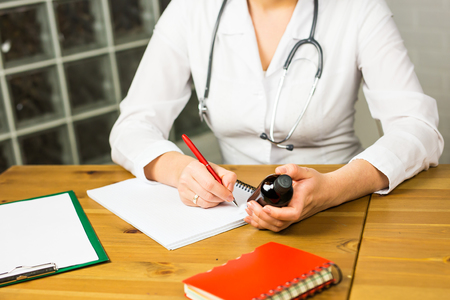 Close-up of female physician medicine doctor or pharmacist sitting at work table, holding jar or bottle of pills in hand and writing prescription on special form. Medical care, pharmacy or health insurance concept.