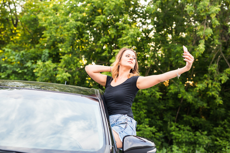 lady on phone: Smiling young woman taking selfie picture with smart phone camera outdoors in car