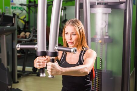 execute: young fitness woman execute exercise with exercise-machine in gym