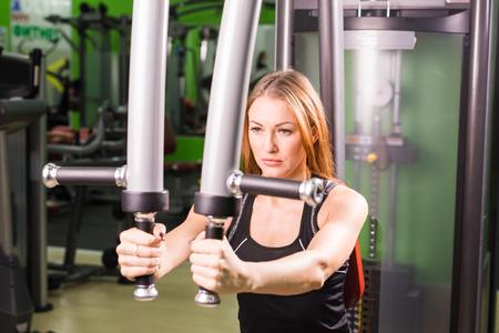 junge Frau, die Übung ausführen Fitness mit Übung-Maschine im Fitness-Studio