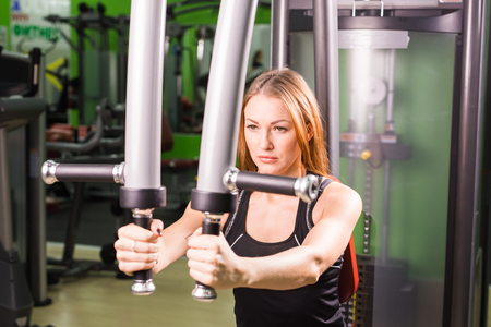 musculation: young fitness woman execute exercise with exercise-machine in gym