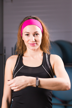 woman on phone: sport, fitness, technology and people concept - young woman with activity tracker and smartphone in gym