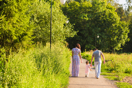 Rear View Of Family Going For Walk In Summer Countryside.
