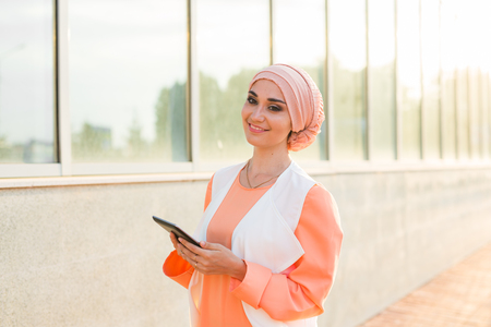 religious clothing: pretty modern Arabian woman with tablet computer outdoors