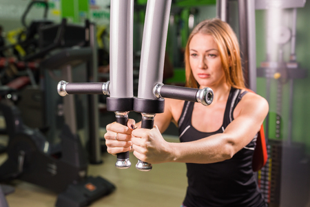 execute: beautiful muscular fit woman exercising building muscles