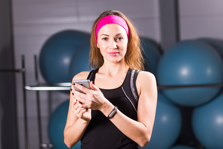 sport, fitness, technology and people concept - young woman with activity tracker and smartphone in gym