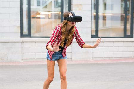 Beautiful young woman with long hair wearing virtual reality headset in an urban context