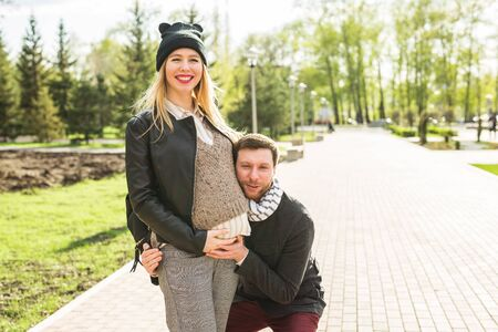 happy pregnant woman and her husband in the park