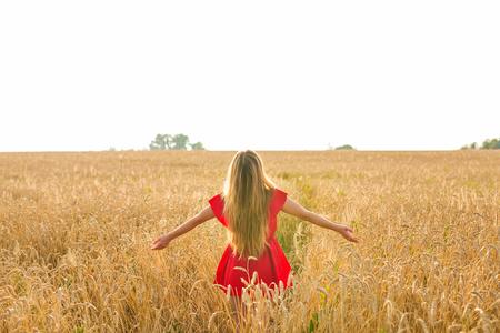 woman on wheat field, rear view in sunlight