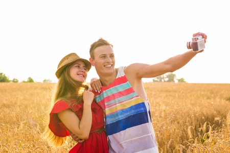 Young happy couple taking a selfie in the field