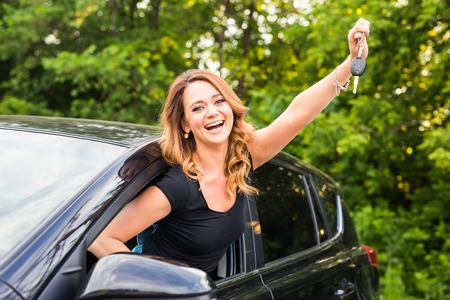 windows and doors: Beautiful young woman driver showing car keys in hand
