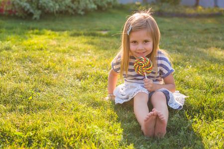 여름에 잔디에 롤리팝 먹는 귀여운 소녀. 스톡 콘텐츠