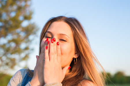 embarrassment: Surprised young woman covering her mouth with hands outdoors