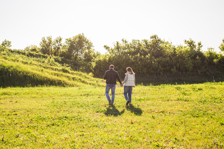 two people fertility: Man and woman holding hands and walking on nature, back view