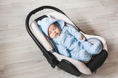 Portrait of cute mixed race baby boy sitting in car seat. Child transportation safety Standard-Bild
