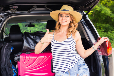Travel, tourism - woman sitting in the trunk of a car with suitcases, showing thumb up sign, ready to leave for vacations. Stock Photo
