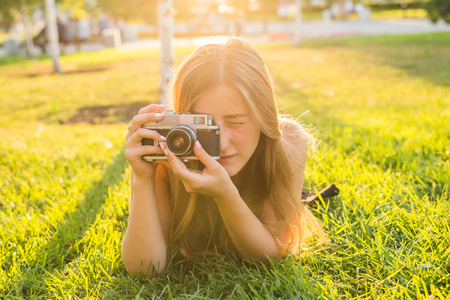 Beautiful girl photographer holds a camera and lying on the grass in the spring outdoors in the park. The concept of tourism and travel. Stock Photo