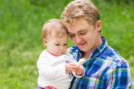 Portrait of happy father and his adorable little daughter in nature Stock Photo