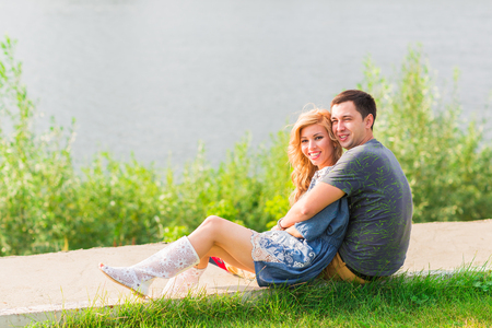 A young couple is romantic in the park on a lake. Man and woman sit in the summer sun in the green grass Stock Photo