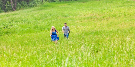Happy couple running on a meadow in summer nature