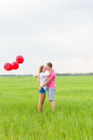 beautiful young couple hugging and kissing in a field with colored balloons.