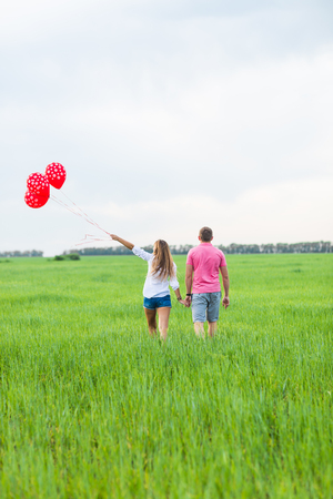 beautiful young couple hugging and kissing in a field with colored balloons, rear view
