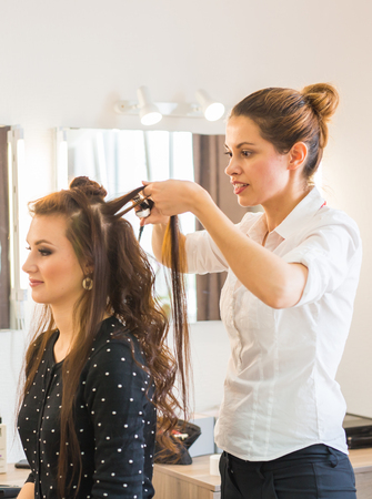 Hairdresser doing haircut for women in hairdressing salon. Concept of fashion and beauty. Positive emotion. Stock Photo