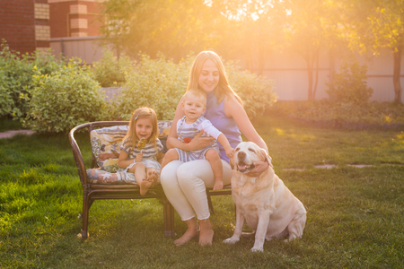 Happy mother and two children with Golden Retriever dog in the garden. Stock Photo