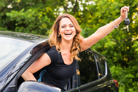 Young happy woman in the car with keys in hand - concept of buying car.