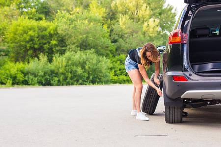 beautiful young pretty woman repairing the car.
