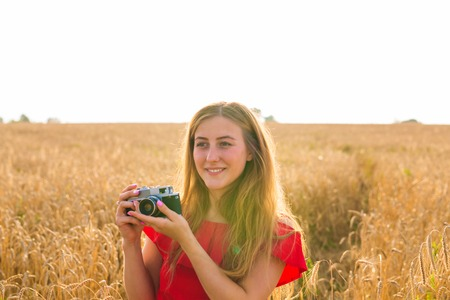 Portrait of beautiful young smiling woman with camera in the field