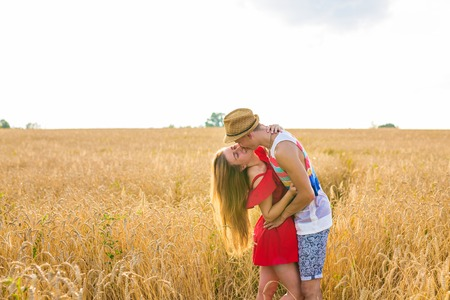 Young love couple kissing on field in sunlight