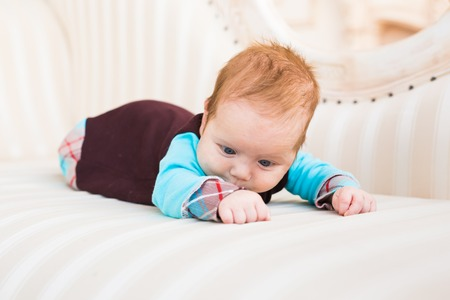 tot: Portrait of a cute newborn baby lying on its stomach and smiling Stock Photo