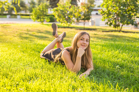 audio book: Girl listening to music streaming with headphones in summer on a meadow