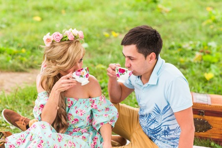Beautiful Young Couple Having Picnic in Countryside. Happy Family Outdoor. Smiling Man and Woman relaxing in Park. Relationships Stock Photo