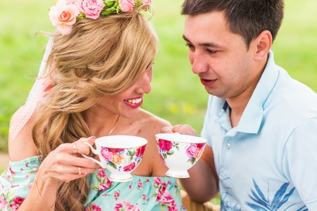 Couple drinking tea on picnic in park, man and woman with cup outdoors on dating. Concept of male and female hands love.
