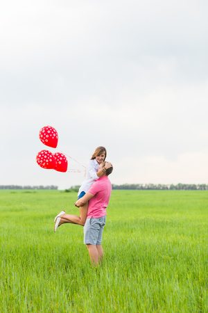 beautiful young couple hugging and kissing in a field with colored balloons Stock Photo