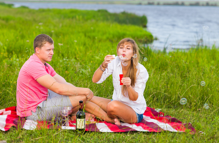 love blow: Beautiful couple having a picnic in nature and blowing bubbles
