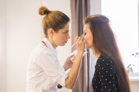 make-up artist doing makeup beautiful girl in the salon, beauty concept and style
