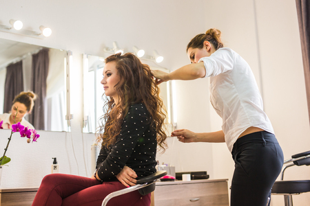 beauty and people concept - happy young woman with hairdresser at hair salon. Stock Photo