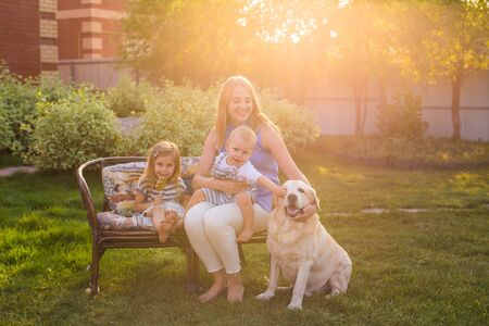 family, pet, domestic animal and people concept - happy family with labrador retriever dog summer garden