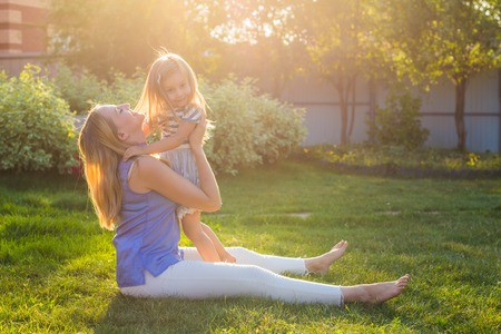 happy harmonious family outdoors. mother laughing and playing with baby daughter girl in the summer on the nature Stock Photo